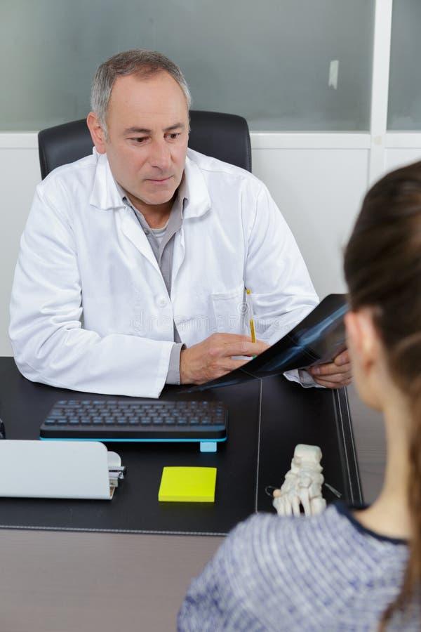Docteur expliquant des résultats de rayon X au patient photographie stock libre de droits