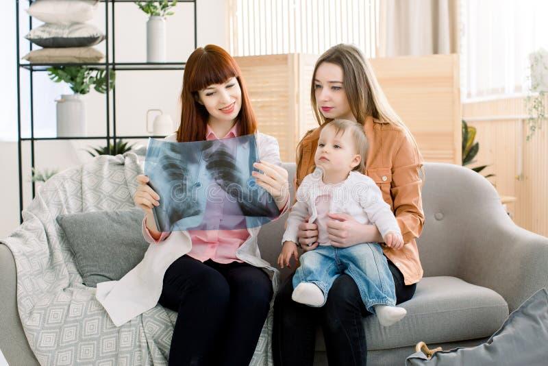 Docteur expliquant l'image de radiographie de la poitrine à la mère avec peu de fille, s'asseyant sur le sofa gris dans la cliniq photos stock
