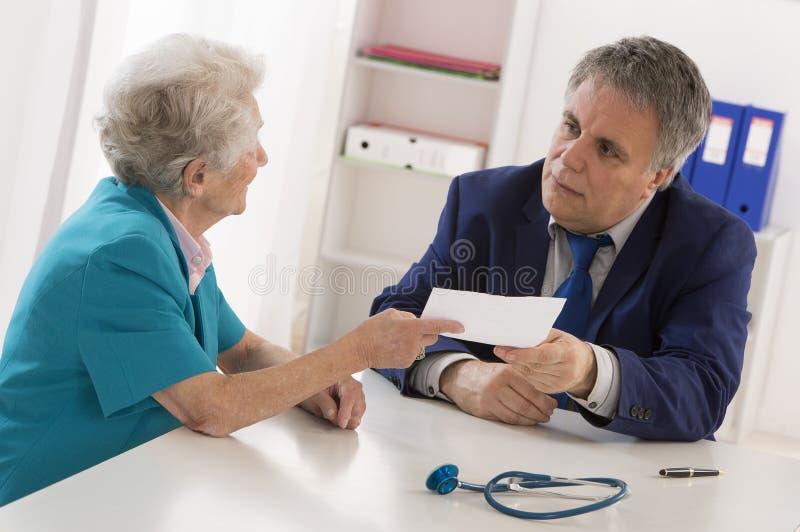Docteur expliquant le diagnostic à son patient photo stock