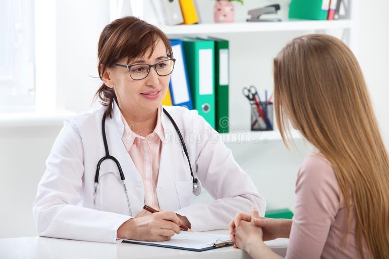 Docteur expliquant le diagnostic à son patient féminin images libres de droits