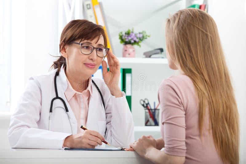 Docteur expliquant le diagnostic à son patient féminin photographie stock