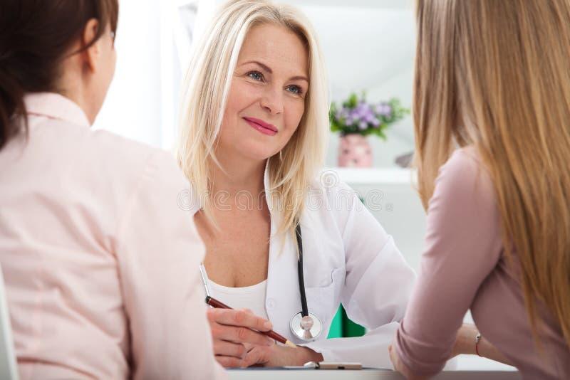 Docteur expliquant le diagnostic à son patient féminin image stock