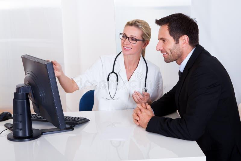 Docteur expliquant quelque chose à un patient masculin photographie stock libre de droits