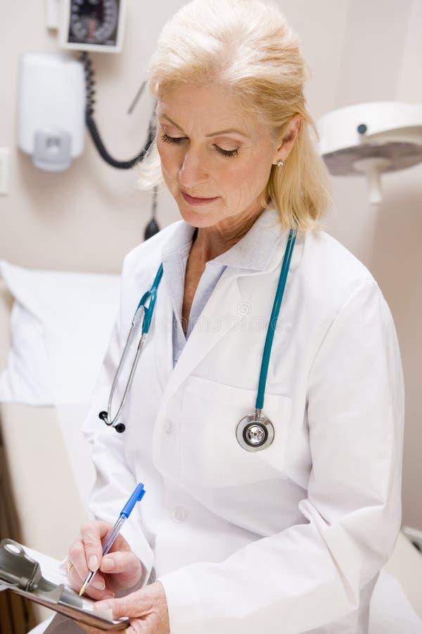 Docteur féminin âgé moyen Writing On A Clipboard photo stock