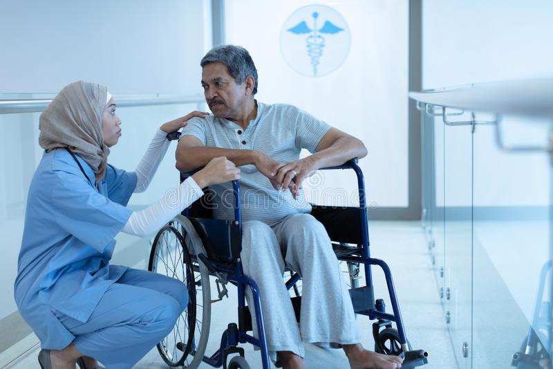 Docteur féminin agissant l'un sur l'autre avec le patient masculin handicapé dans le couloir image stock