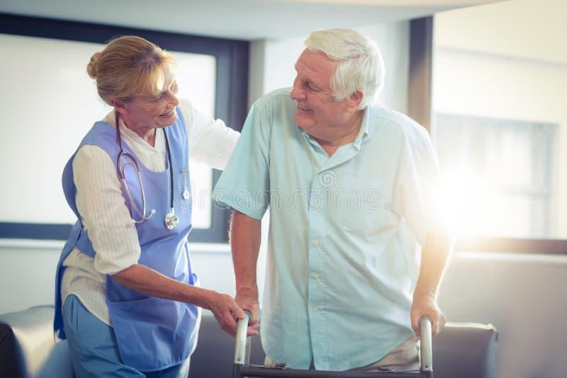 Docteur féminin aidant l'homme supérieur à marcher avec le marcheur image stock