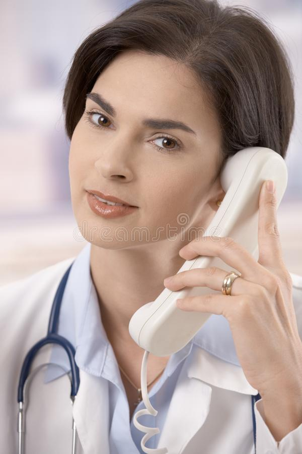 Docteur féminin au téléphone image stock