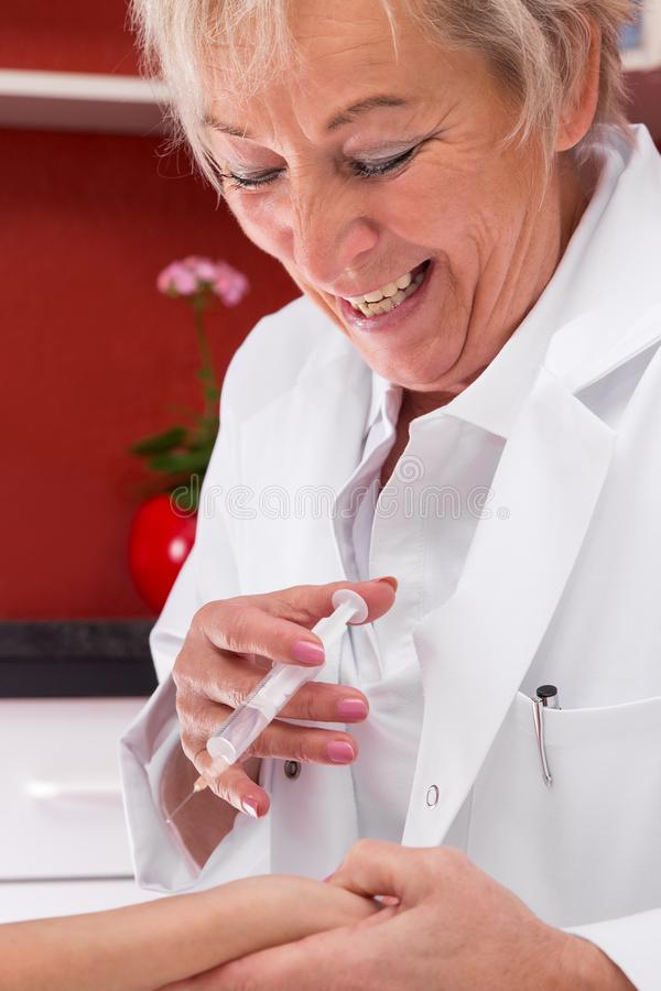 Docteur féminin avec la seringue ayant l'amusement photos libres de droits