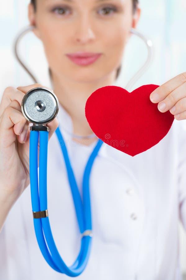 Docteur féminin avec le stéthoscope tenant le coeur rouge image libre de droits