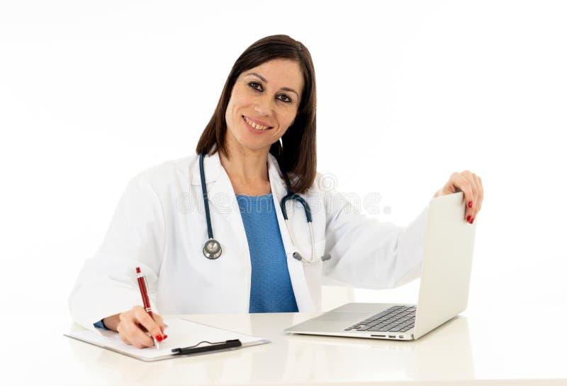 Docteur féminin ayant la consultation en ligne avec le patient et travaillant sur l'ordinateur portable d'isolement sur le blanc photo stock