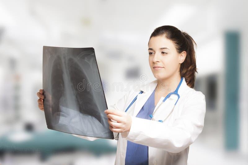 Docteur féminin caucasien regardant une radiographie images stock