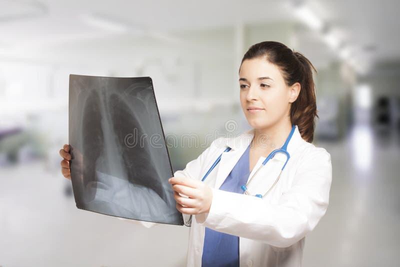 Docteur féminin caucasien regardant une radiographie photographie stock libre de droits