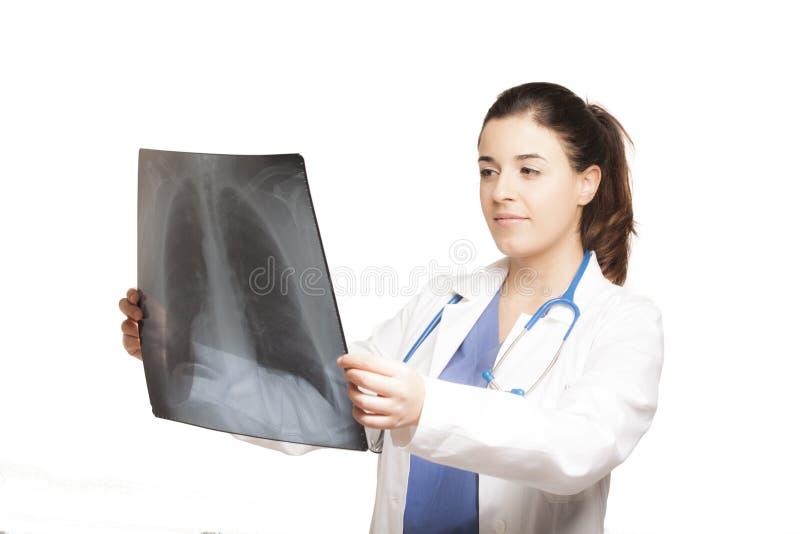 Docteur féminin caucasien regardant une radiographie d'isolement image stock