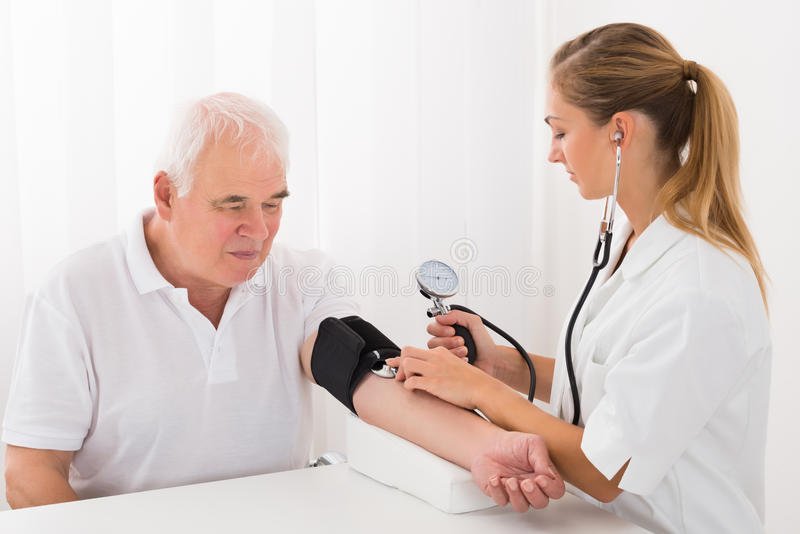 Docteur féminin Checking Blood Pressure du patient masculin images libres de droits