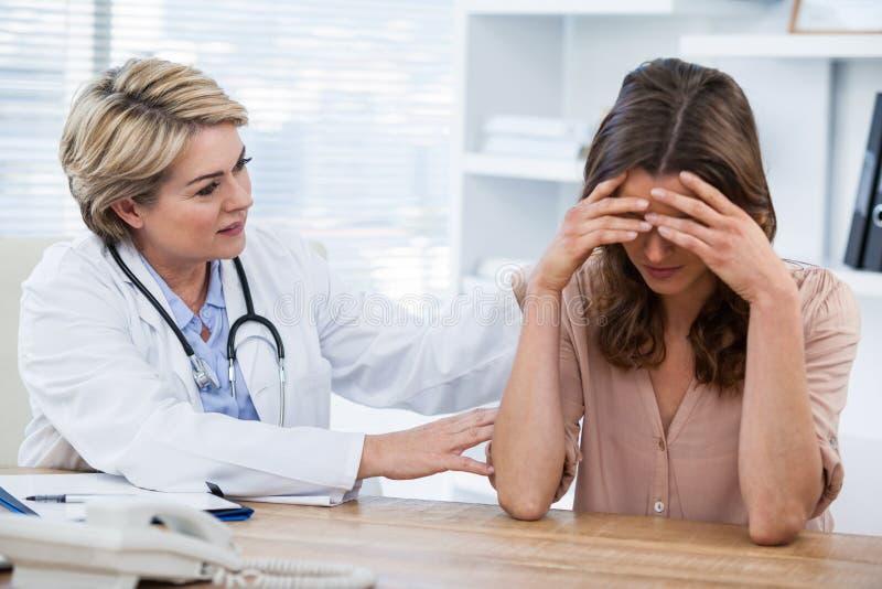 Docteur féminin consolant un patient images libres de droits