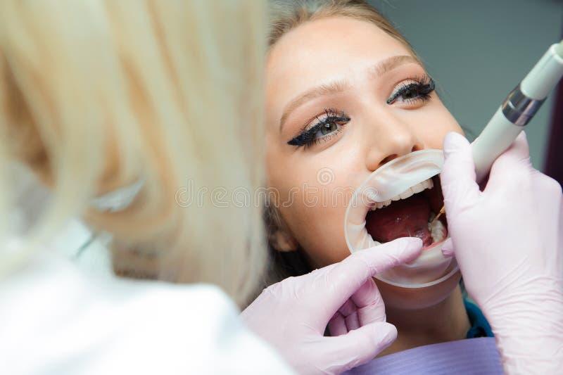 Docteur féminin dans l'uniforme vérifiant vers le haut des dents du patient féminin dans la clinique dentaire image stock