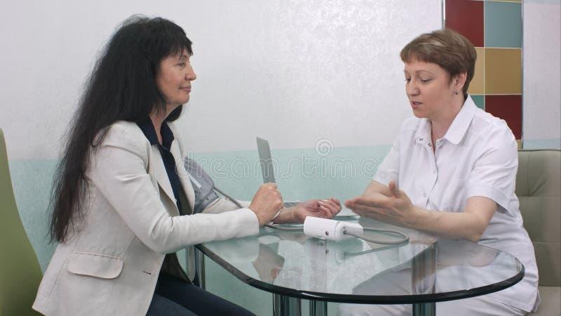 Docteur féminin dans la tension artérielle médicale blanche de patients d'essai de manteau tout en parlant et se reposant dans le photo stock