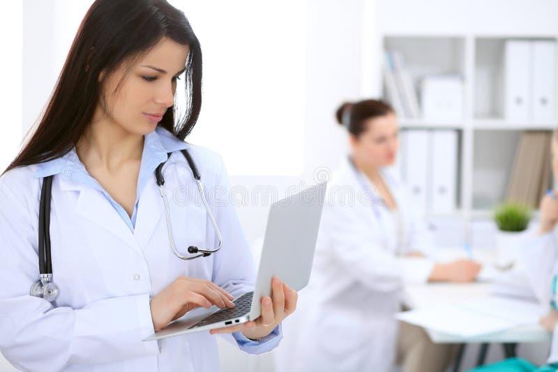 Docteur féminin de brune sur le fond des collègues parlant entre eux dans l'hôpital images libres de droits