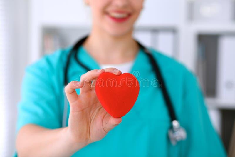 Docteur féminin de chirurgien avec le stéthoscope tenant le coeur images stock