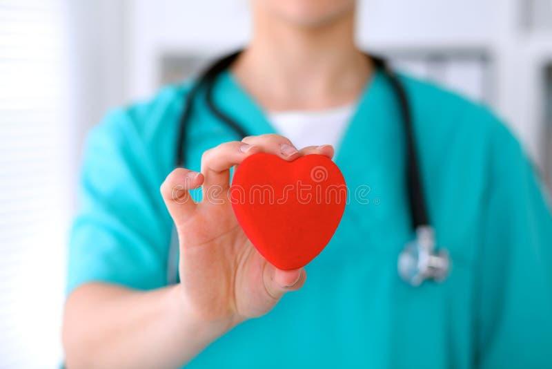 Docteur féminin de chirurgien avec le stéthoscope tenant le coeur images libres de droits