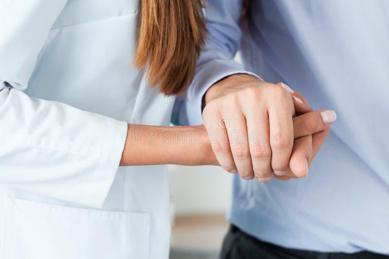 Docteur féminin de médecine aidant son patient à marcher après operati images stock