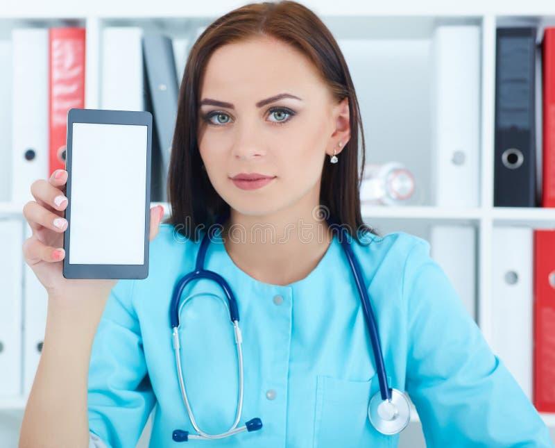 Docteur féminin de médecine tenant le téléphone portable et le montrant à l'appareil-photo Matériel médical, technologie moderne  photographie stock