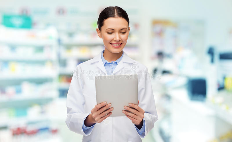 Docteur féminin de sourire avec le PC de comprimé à la pharmacie photographie stock