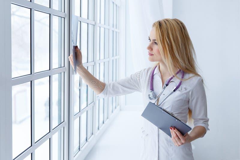 Docteur féminin de sourire de jeunes avec le stéthoscope regardant le rayon X le bureau du ` s de docteur photos libres de droits