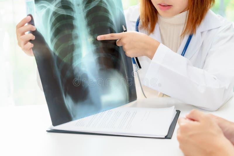 Docteur féminin examinant au sujet des poumons avec le film radiographique photo stock
