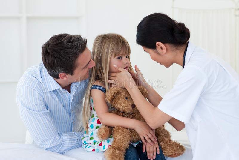 Docteur féminin examinant la petite fille photographie stock libre de droits