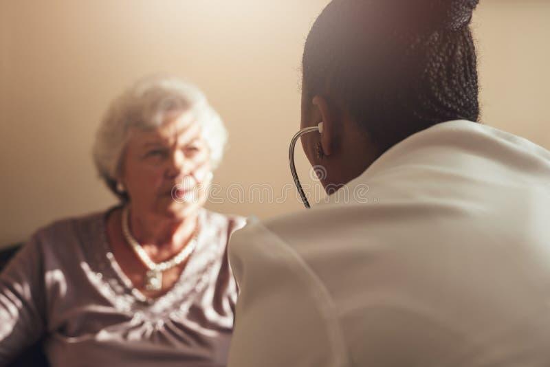 Docteur féminin examinant le patient aîné photo libre de droits