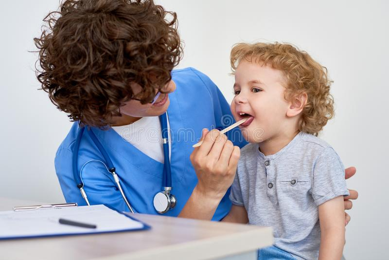 Docteur féminin examinant le petit garçon image libre de droits
