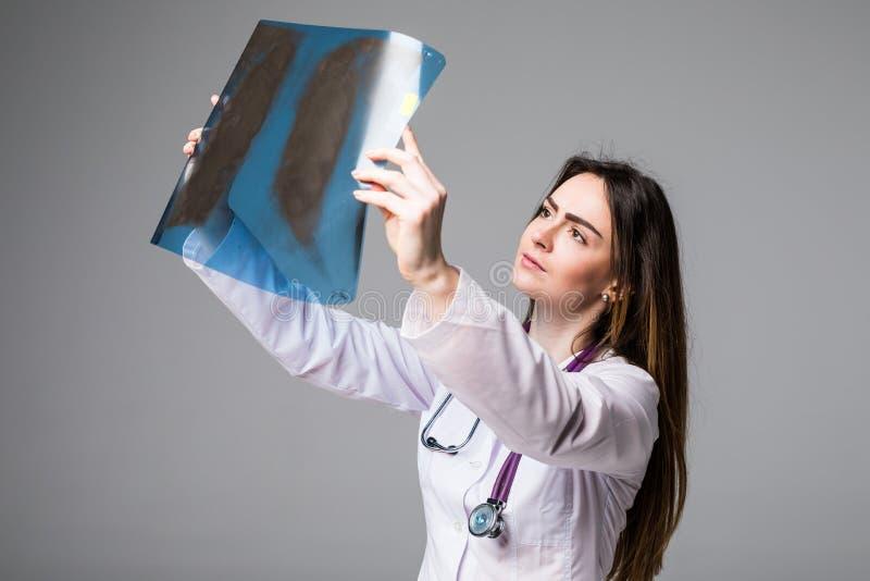 Docteur féminin examinant une image de rayon X Le foyer est sur l'image de rayon X sur le fond gris photo stock