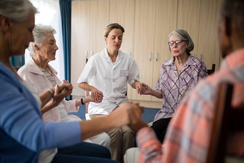 Docteur féminin méditant tout en tenant des mains avec des aînés photographie stock