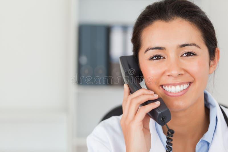 Docteur féminin magnifique sur le téléphone et la pose images libres de droits