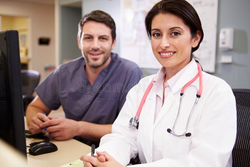 Docteur féminin With Male Nurse travaillant à la station d'infirmières images libres de droits