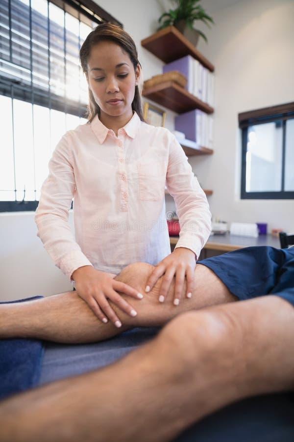 Docteur féminin massant le genou du patient masculin photos stock