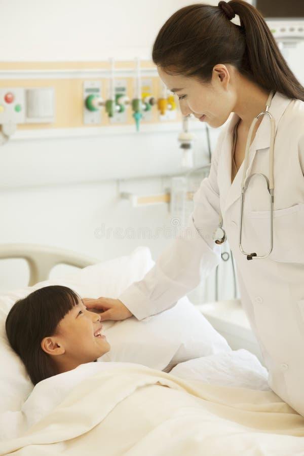 Docteur féminin parlant au patient de fille se couchant sur un lit d'hôpital image stock