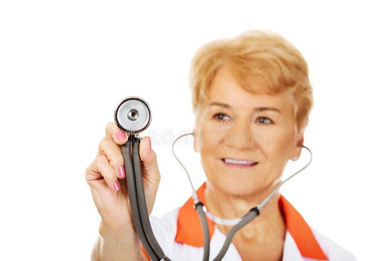 Docteur féminin plus âgé de sourire tenant le stéthoscope images libres de droits