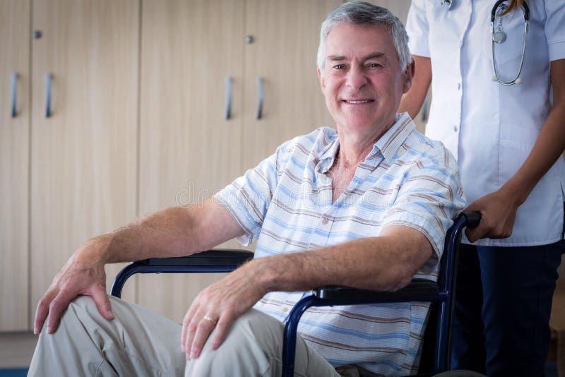 Docteur féminin portant l'homme supérieur sur le fauteuil roulant photographie stock libre de droits