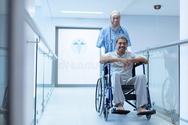 Docteur féminin poussant le patient masculin dans le fauteuil roulant au couloir photos stock