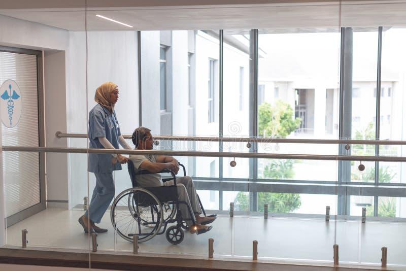 Docteur féminin poussant le patient masculin dans le fauteuil roulant au couloir photo libre de droits
