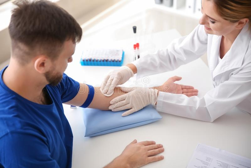 Docteur féminin préparant le patient pour l'aspiration de sang dans la clinique photographie stock libre de droits