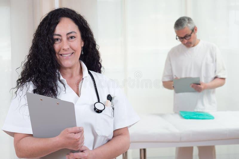 Docteur f?minin regardant la cam?ra et le fonctionnement masculin d'infirmi?re photos libres de droits
