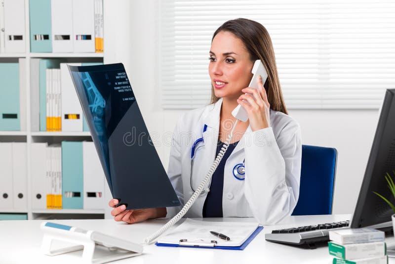 Docteur féminin regardant le rayon X de patients dans son bureau image libre de droits