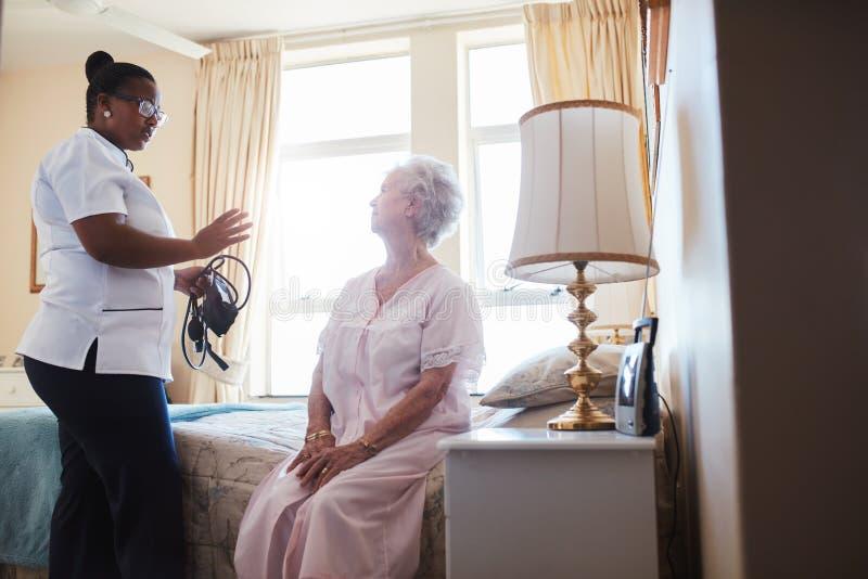 Docteur féminin rendant visite à son patient supérieur à la maison image libre de droits