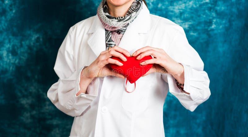 Docteur féminin retenant un coeur rouge photos stock