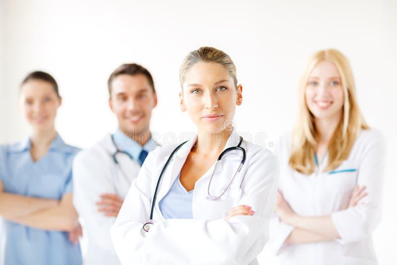 Docteur féminin sérieux devant le groupe médical photographie stock libre de droits