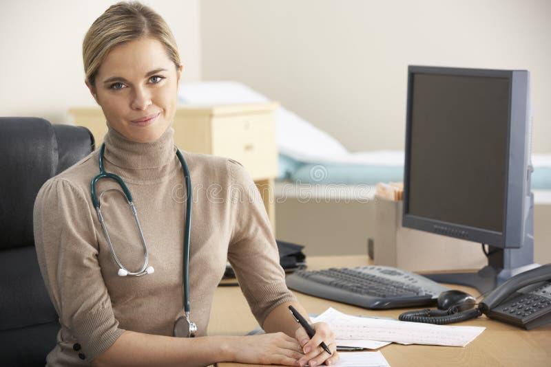 Docteur féminin s'asseyant au bureau image stock