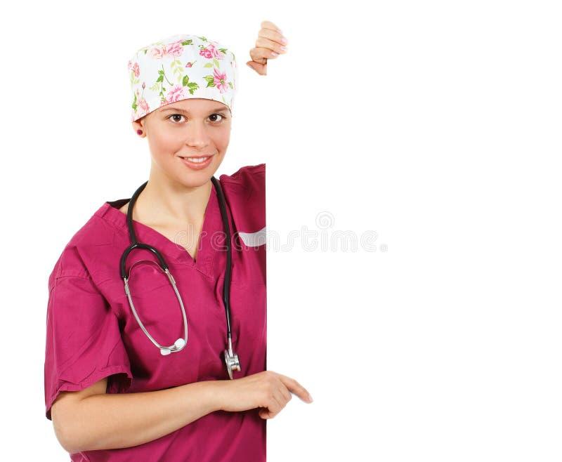 Docteur féminin se dirigeant sur un panneau blanc photographie stock
